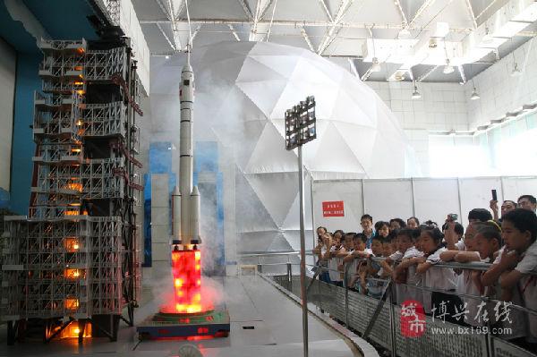 """在山东科技馆,参加夏令营的农村儿童正在观看""""神舟十号""""飞船模拟发射"""