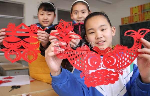 小学生窗花_几名小学生正在展示自己剪出的窗花.