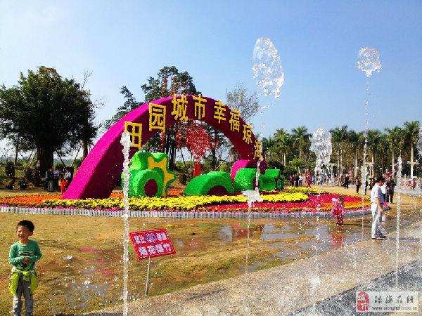"""""""田园城市幸福琼海""""的大型花雕竖立在万泉河音乐喷泉广场上,许多游人"""