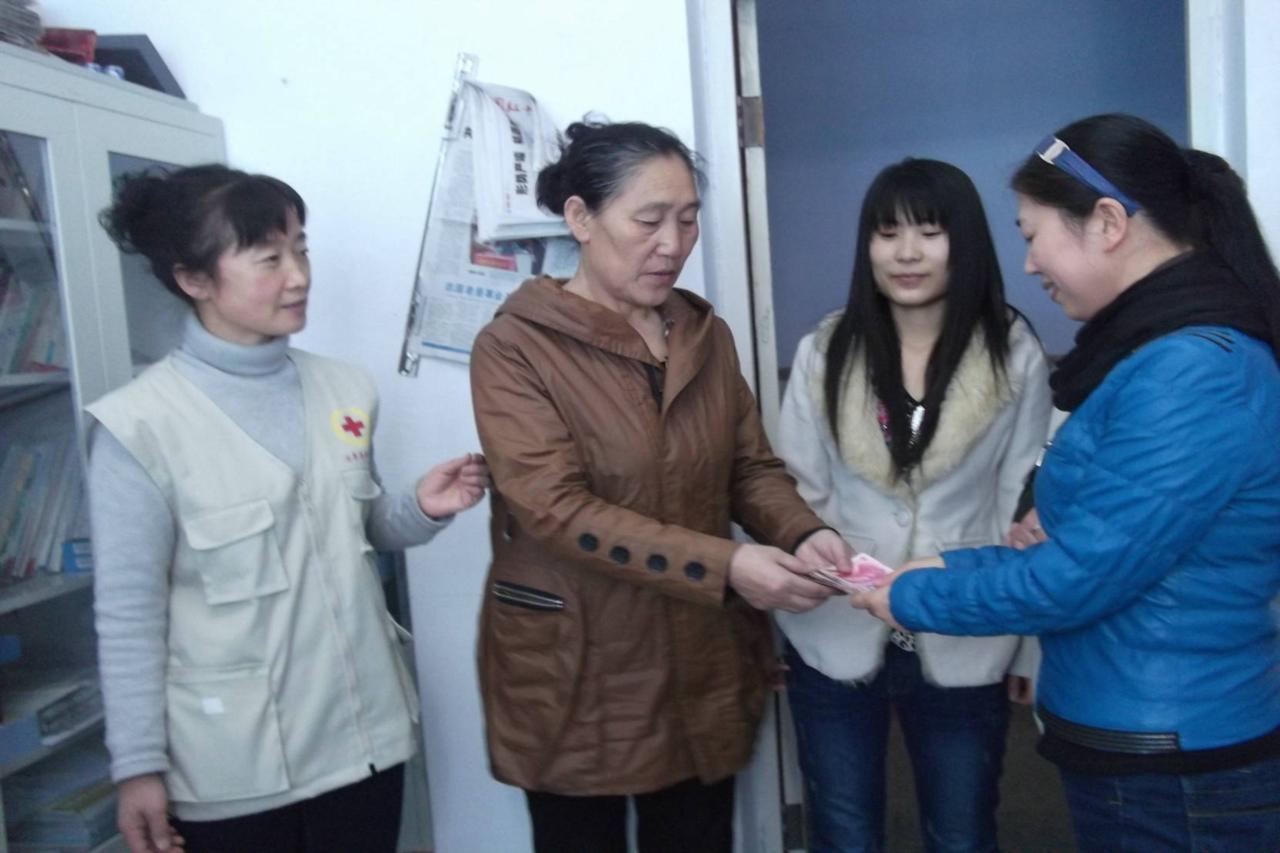 爱心志愿者陈志华将善款2200元交到患病女孩王婉玲的奶奶杨彩凤手里